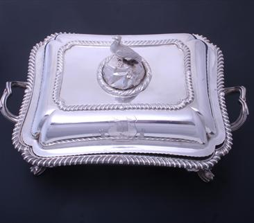 A William IV sterling silver entree dish and cover with armorial finial on electroplate two handled stand
