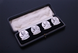 A charming set of four modern sterling silver armorial menu or card holders