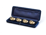A fine and rare set of four George V 9ct rose gold armorial menu holders